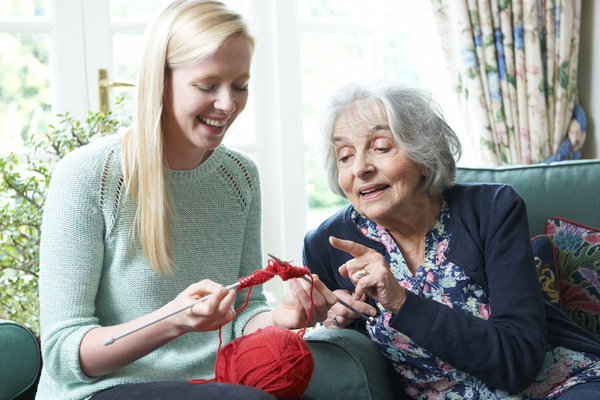 Image of a young woman knitting with her grandmother
