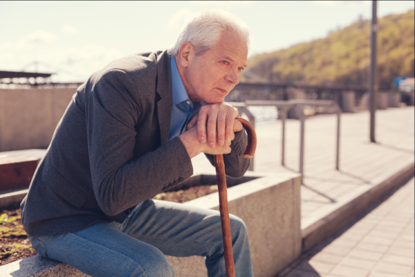image of an older man sitting on a bench contemplating