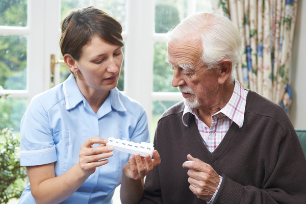 Image of a home health nurse helping a senior man with his pill box