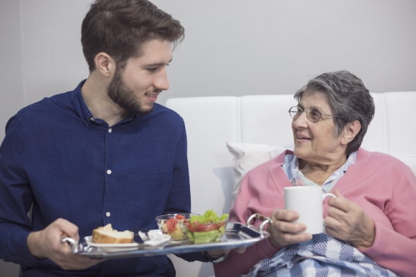 Young man eating lunch with a senior female relative