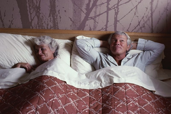 Married couple asleep in bed
