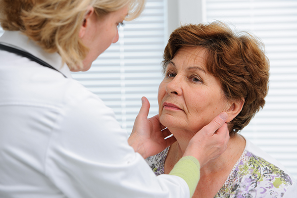 Image of a doctor feeling a woman's neck to check for swelling