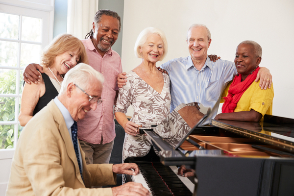Image of a group of seniors singing around a piano