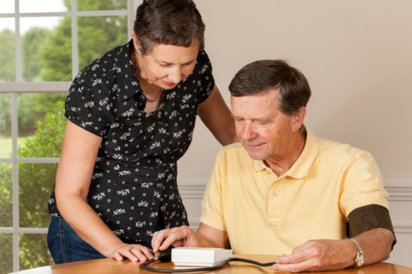 A man and his wife looking at his home heart monitor