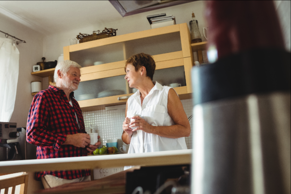 Image of an adult daughter talking to her father in her kitchen